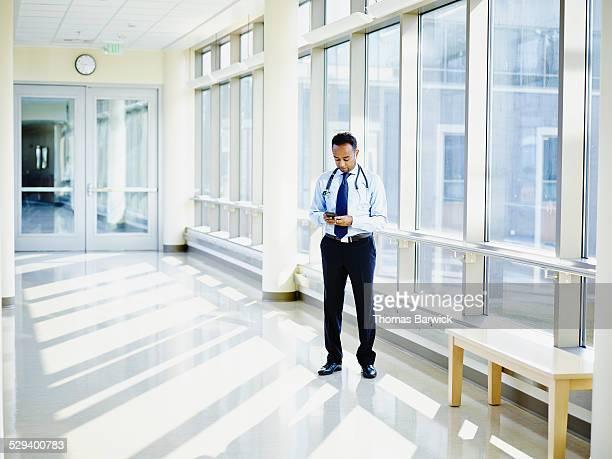 Doctor working on smartphone in hospital corridor