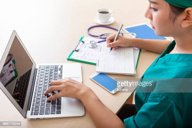 Doctor working with laptop and mobile in room.
