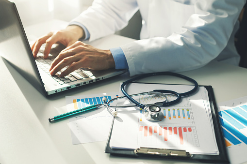 doctor working with medical statistics and financial reports in office 1056799938