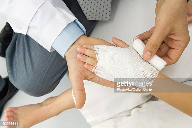 Doctor wrapping a patient's hand in gauze, high angle view