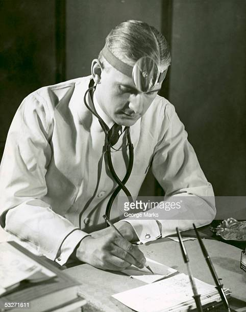 doctor writes at his desk - 20th century stock pictures, royalty-free photos & images