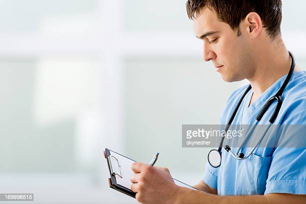 Doctor writing a medical chart.