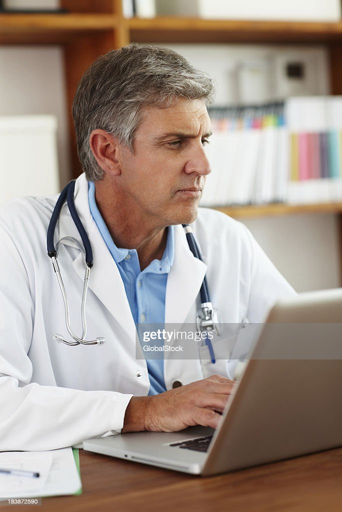 Doctor writing a patient's journal : Stock Photo
