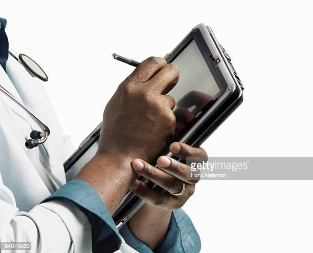 doctor writing in an electronic notepad - escriba fotografías e imágenes de stock