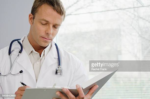 Doctor writing in file