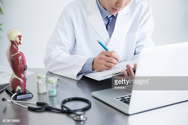 Doctor writing medical record while watching laptop