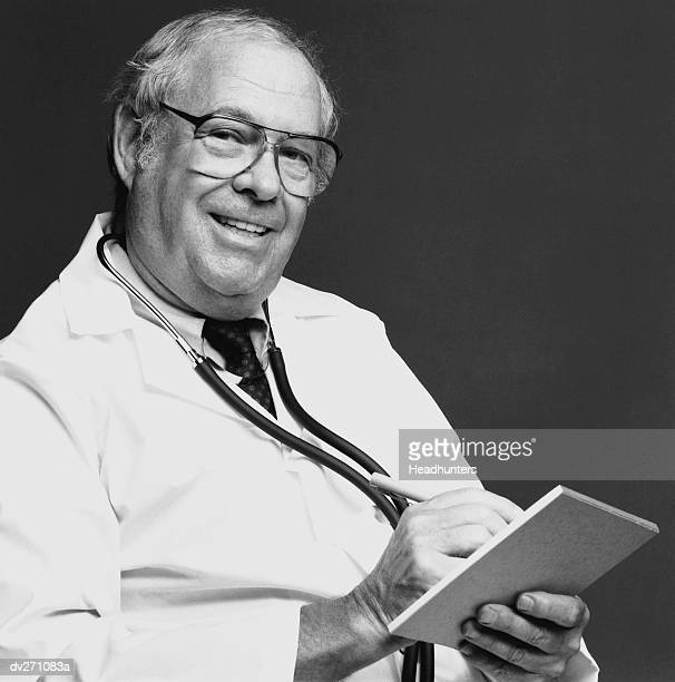 doctor writing on pad of paper - headhunters stock pictures, royalty-free photos & images