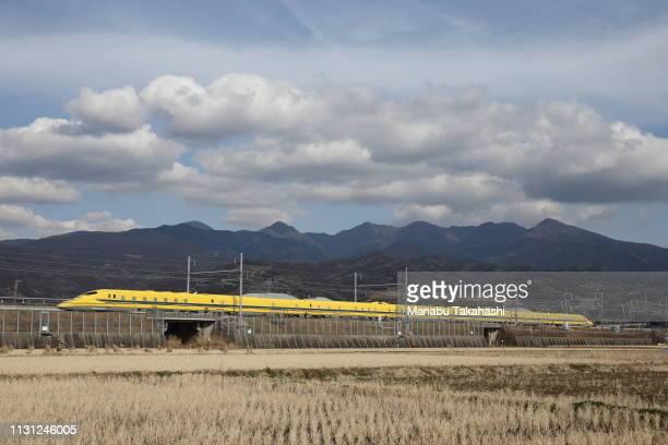A 'Doctor Yellow' test Shinkansen bullet train runs between Mishima and ShinFuji stations on January 29 2015 in Fuji Shizuoka Japan