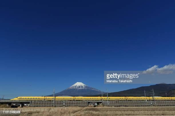 A 'Doctor Yellow' test Shinkansen bullet train runs past Mt Fuji between Mishima and ShinFuji Stations on February 3 2017 in Fuji Shinagawa Japan