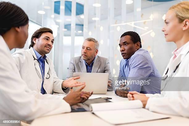 Los médicos y las personas de negocios de la comunicación sobre una reunión.