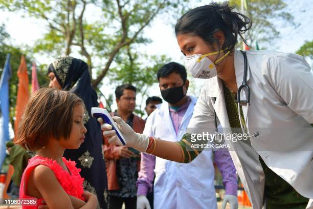 Doctors and health workers check the body temperature of people coming from Bangladesh at the IndiaBangladesh border in Agartala on February 2 2020 A...
