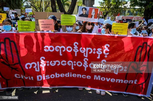 Doctors and health workers hold a banner and signs as they take part in a protest against the military coup in front of the Chinese embassy in Yangon...