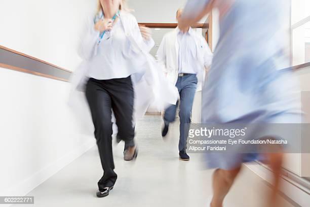 Doctors and nurse running in hospital corridor
