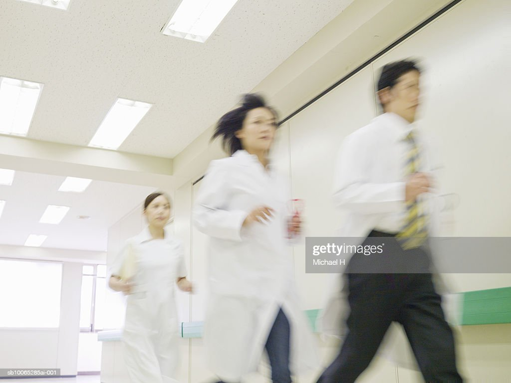 Doctors and nurse running in hospital corridor : Foto stock