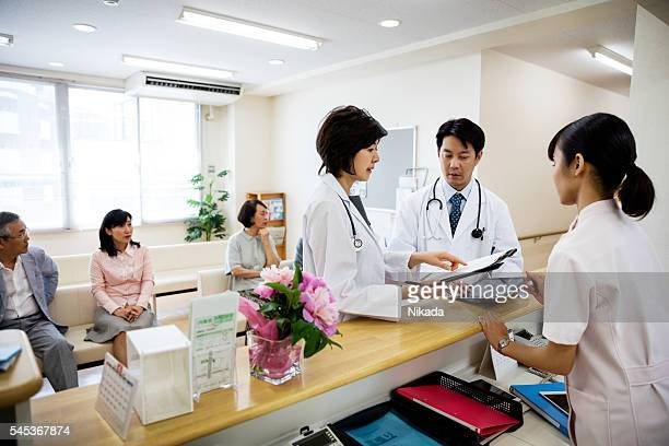 Doctors and nurse standing at reception with patients waiting in