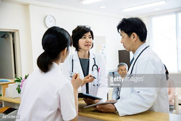 Doctors and nurse standing at reception with patients waiting