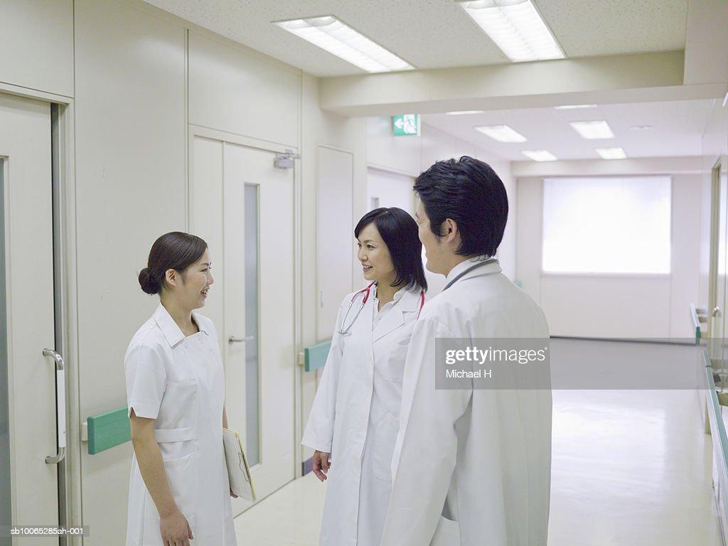 Doctors and nurse talking in hospital corridor : Foto stock