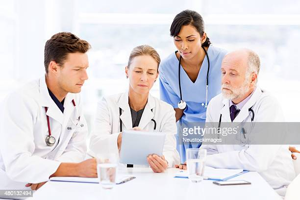 Doctors And Nurse Using Tablet Computer At Conference Table
