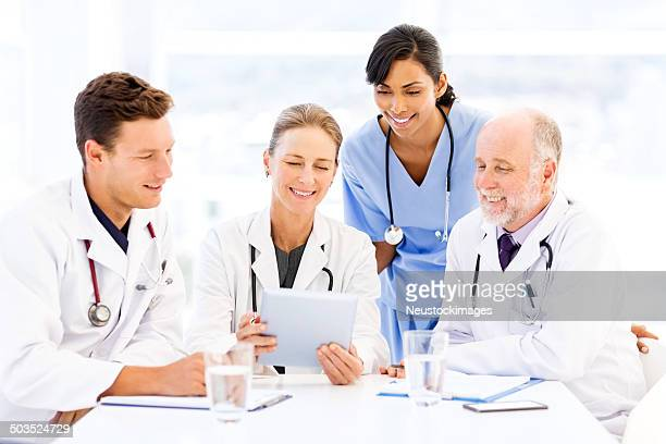 Doctors And Nurse Using Tablet Computer At Table