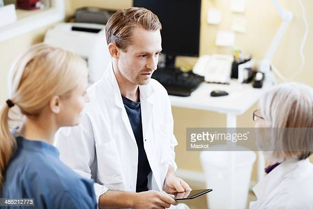 Doctors and nurse with digital tablet discussing in hospital