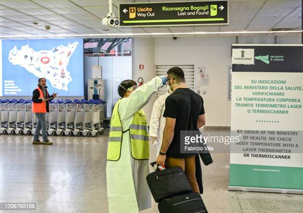 Doctors and nurses carry out health checks on passengers arriving at Catania airport on March 12 2020 in Catania Italy The Italian government has...