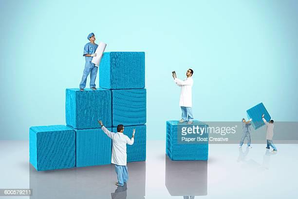 doctors and nurses lifting wooden building blocks