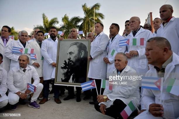 Doctors and nurses of Cuba's Henry Reeve International Medical Brigade pose with a portrait of Cuban late leader Fidel Castro as they are bid...