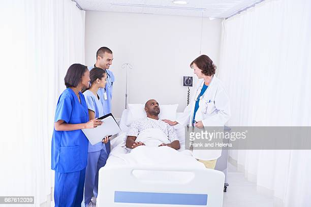 doctors and nurses surrounding patient in hospital bed - surrounding stock pictures, royalty-free photos & images