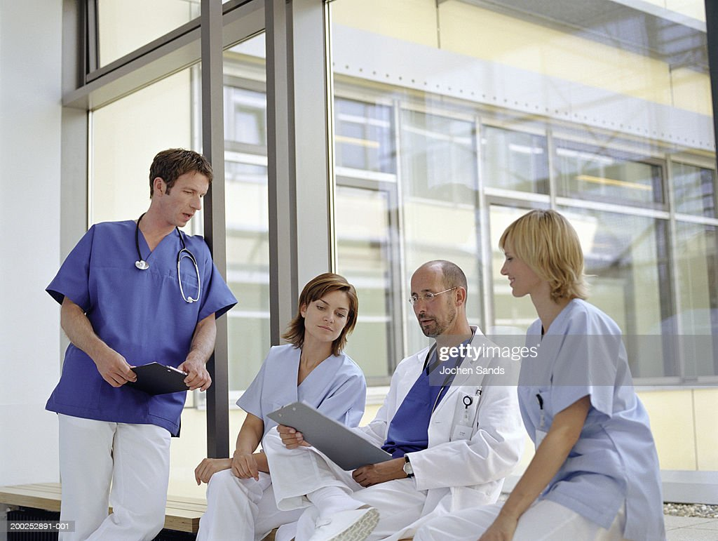 Doctors and nurses talking by window in hospital : Stock Photo