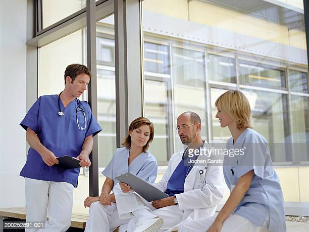 Doctors and nurses talking by window in hospital