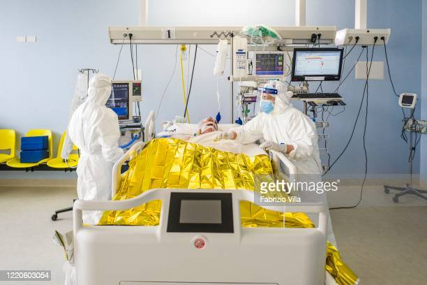Doctors and nurses wear protective overalls with mask goggles and gloves while assisting a patient in the Intensive Care Unit for COVID19 patients at...