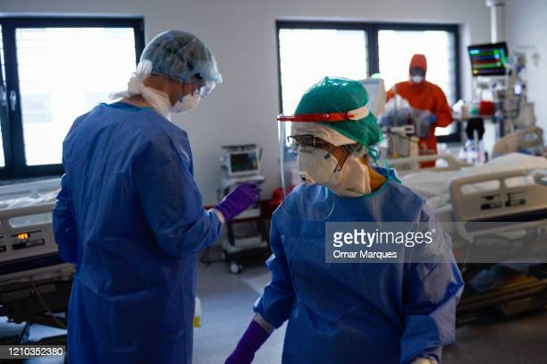 Doctors and nurses wear protective suits masks goggles and gloves as they perform the morning medical checks inside the Intensive Care Unit for COVID...