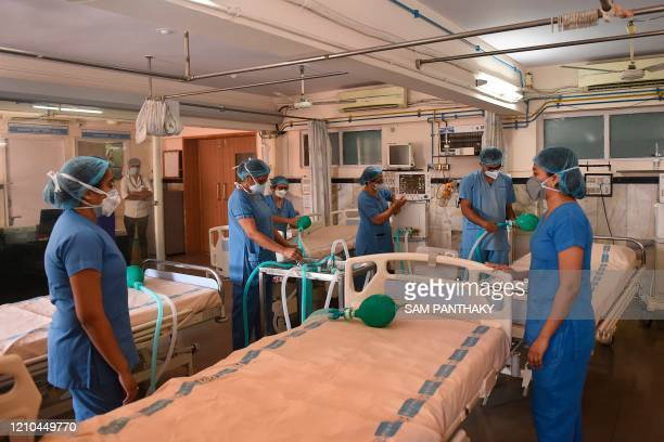 Doctors and nursing staff test a four way multiplexer machine, which splits oxygen supply from a single ventilator to four patients through...