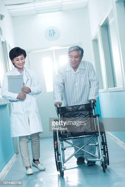 doctors and older men in the hospital corridor - 70 79 jaar stockfoto's en -beelden