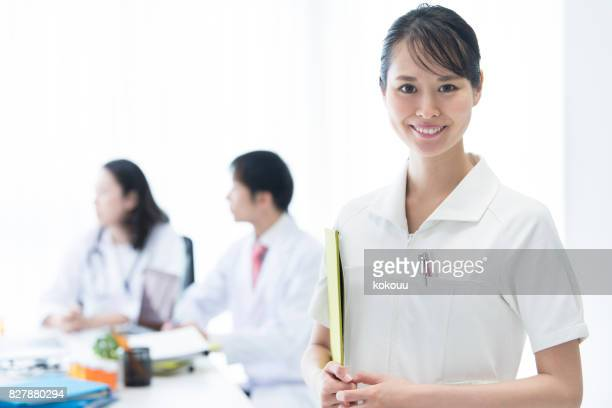 Doctors are meeting and a nurse's woman is staring at the camera.