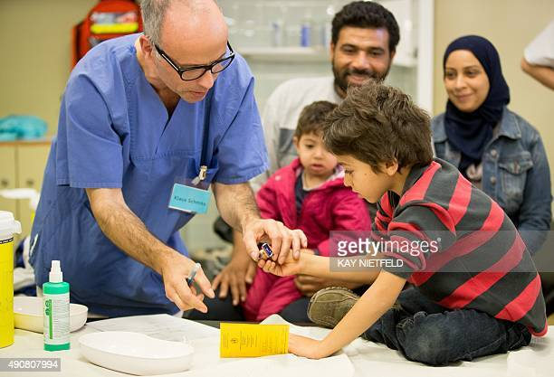 Doctor's assistant Klaus Schmitz helps a young Syrian refugee to stamp his vaccination record as his family looks on at the State Office of Health...