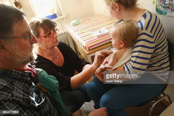 A doctor's assistant prepares 11monthold Tijana for a vaccine against measles rubella mumps and chicken pox as children's doctor Juergen Hochfeld...