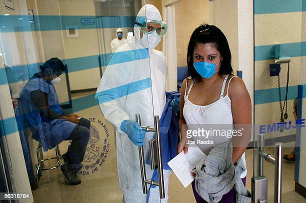 Doctors at the Mexico City Navy Hospital wear protective gear as they tend to a patients complaining of a swine flulike symptoms on May 1 2009 in...