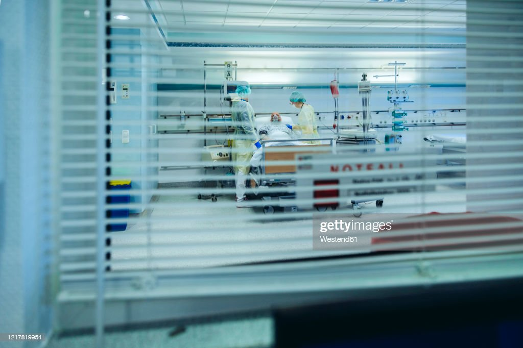 Doctors behind sunblind caring for patient in emergency care unit of a hospital with respiratory equipment : Stockfoto