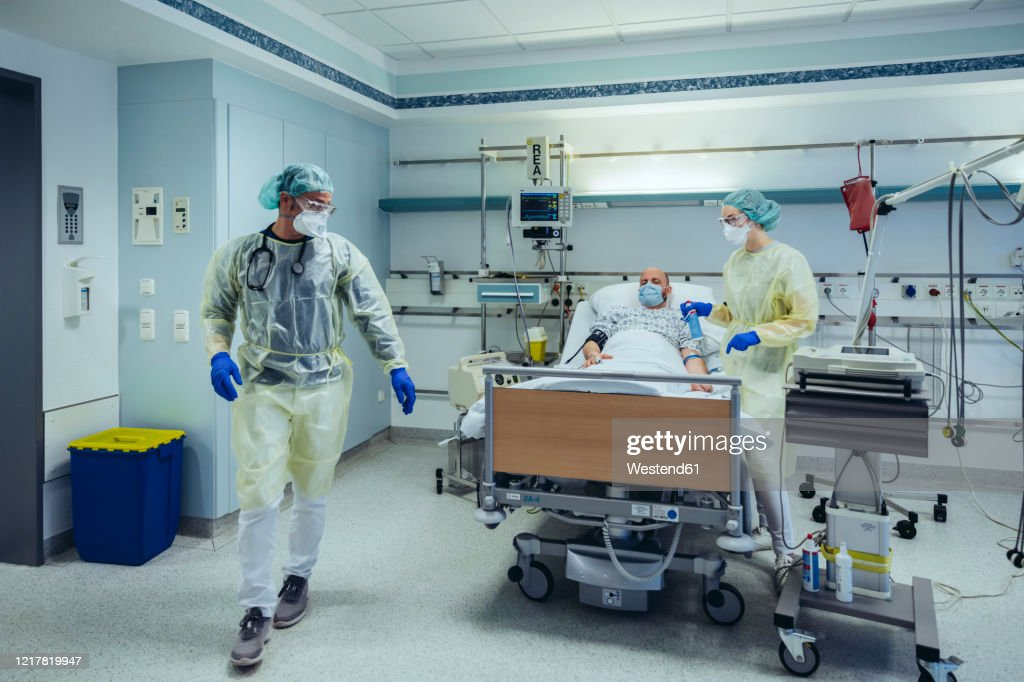 Doctors caring for patient in emergency care unit of a hospital : Stock Photo