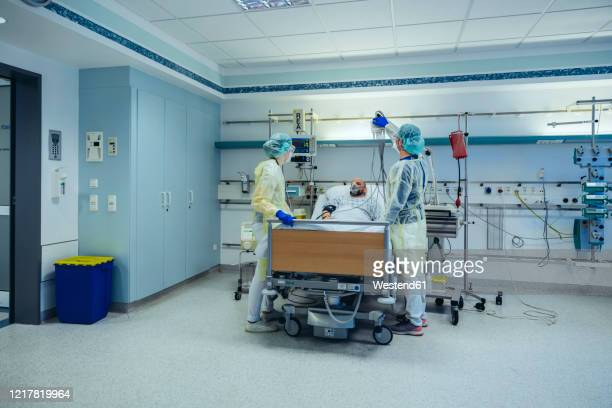 doctors caring for patient in emergency care unit of a hospital with respiratory equipment - intensivstation stock-fotos und bilder