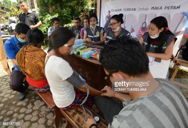 Doctors check Balinese people at an evacuation center after being evacuated from Mount Agung volcano at Rendang in Karangasem Regency on Indonesia's...