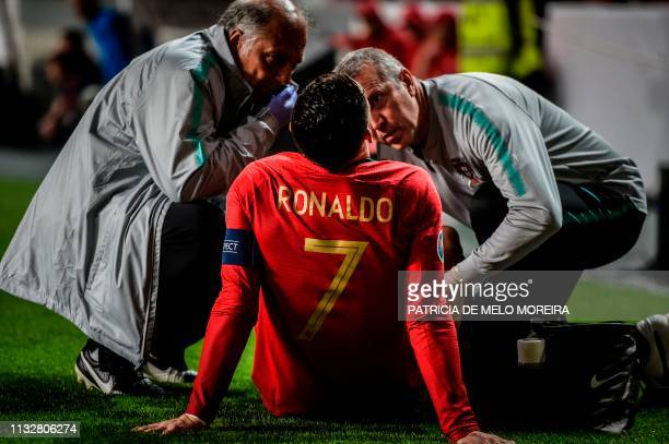 TOPSHOT Doctors check on Portugal's forward Cristiano Ronaldo during the Euro 2020 qualifying group B football match between Portugal and Serbia at...