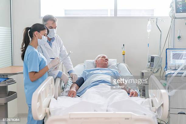 doctors checking on patient at the icu - intensive care unit stock pictures, royalty-free photos & images
