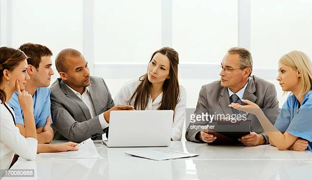 Doctors collaborating with a business team.