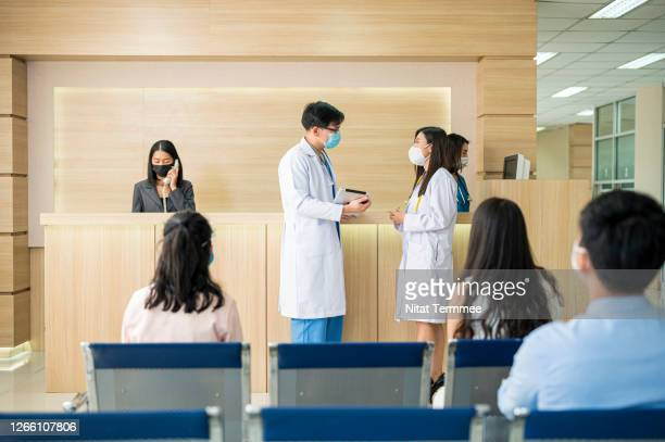 doctors communicating together in front of reception counter. patients waiting in lobby at hospital. they are wearing protective face mask, social distancing. - thai ethnicity stock pictures, royalty-free photos & images