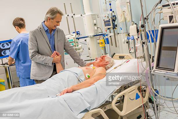 doctors consoling - patient on ventilator stock pictures, royalty-free photos & images