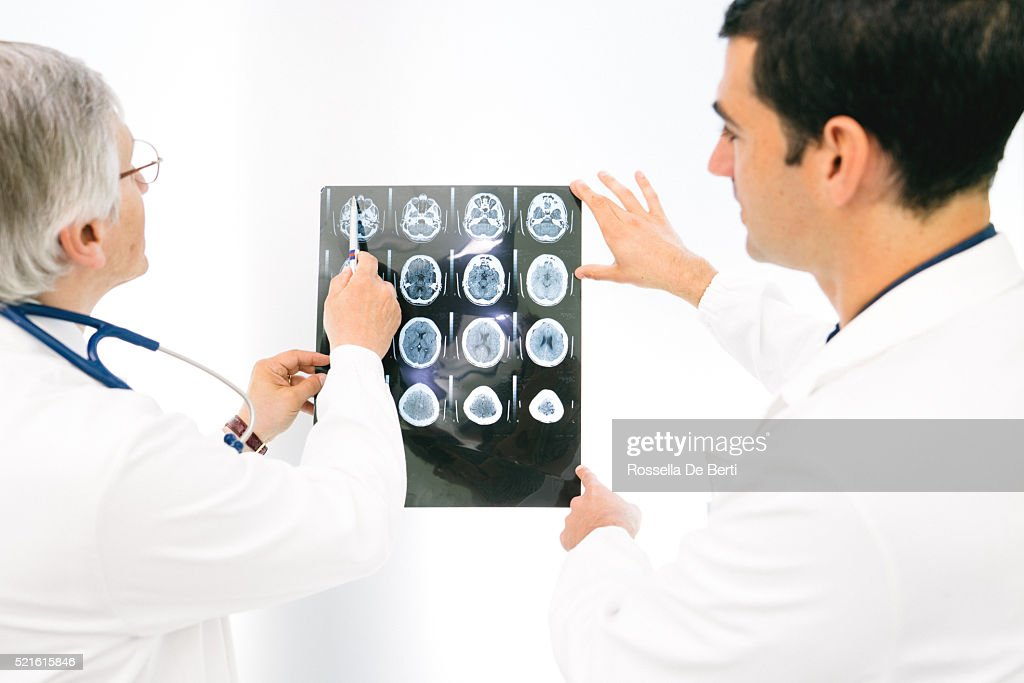 Doctors Consult Over An MRI Scan Of The Brain : Stock Photo