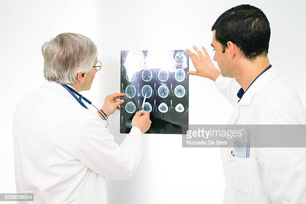Doctors Consult Over An MRI Scan Of The Brain