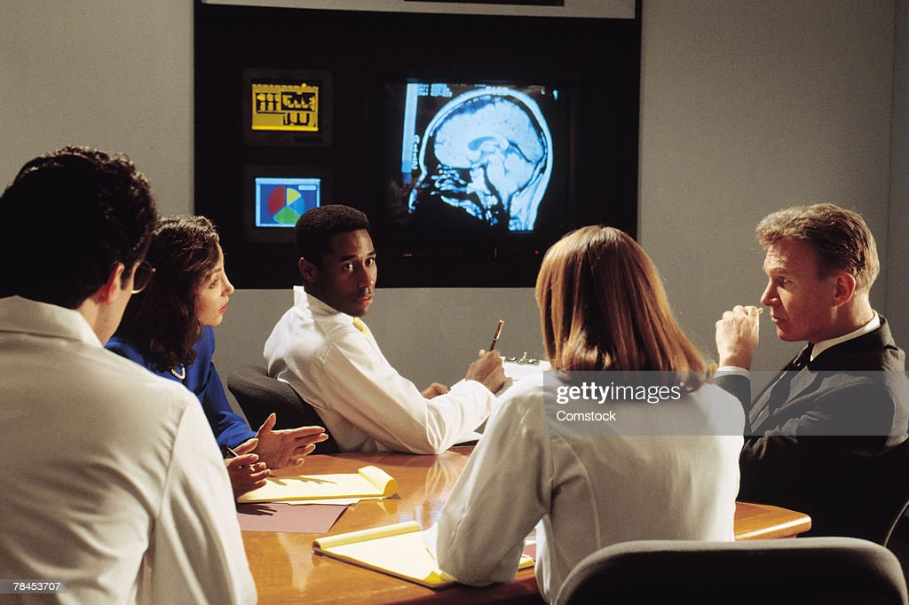 Doctors consulting on diagnosis in conference room : Stockfoto